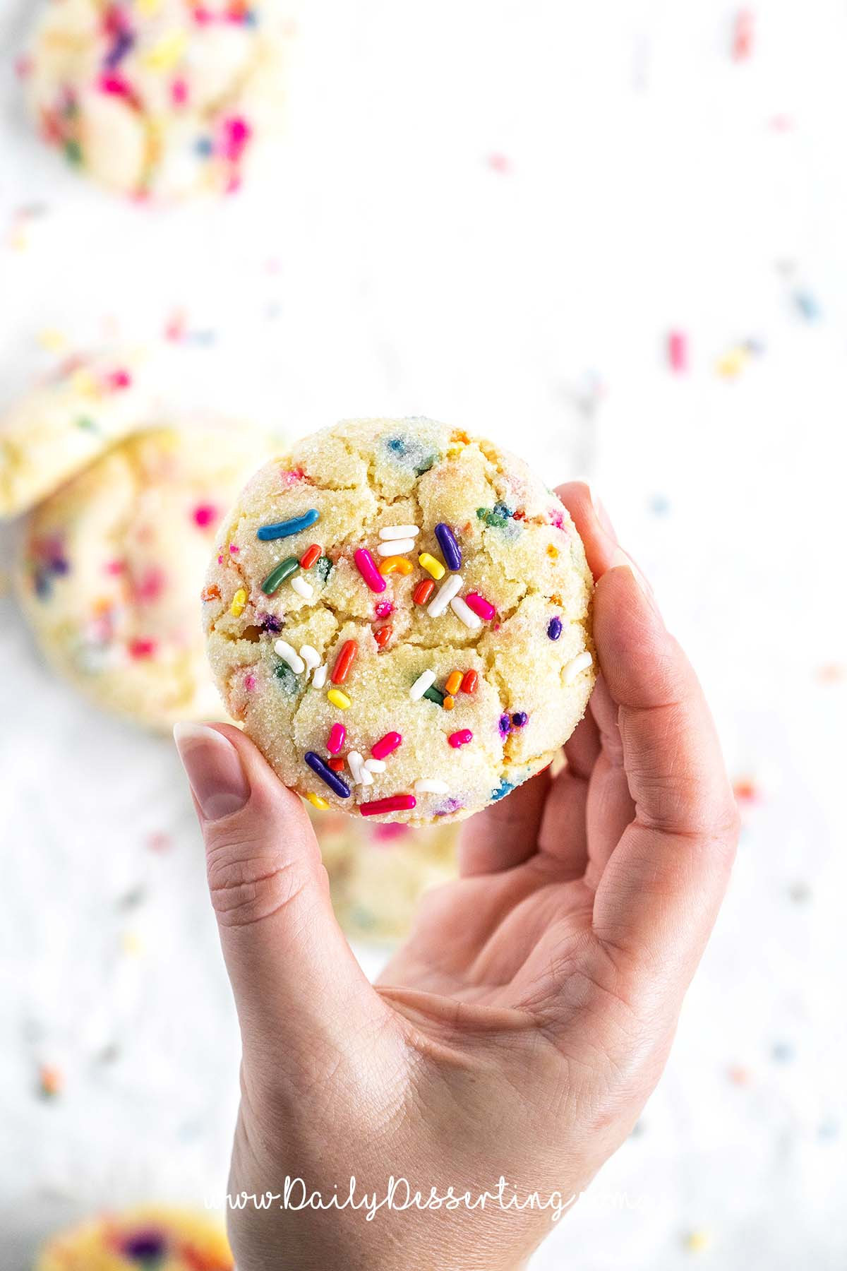 hand holding up one of the best funfetti cookies